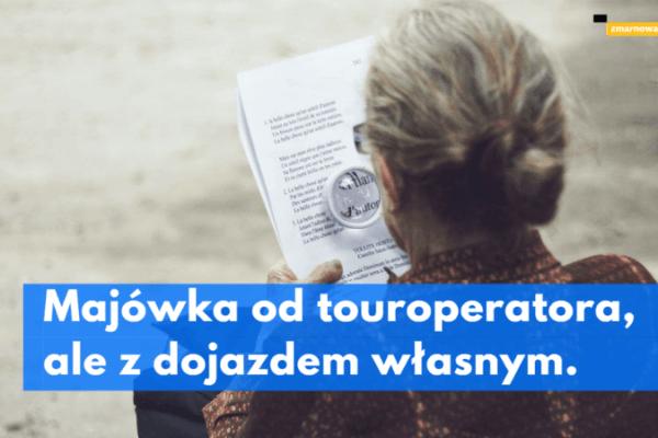 ilustracja wpisu blogowego na teat majówki z touroperatorem i dojazdem własnym starsza pani siedzi odwrócona tyłem do obiektywu w ręku trzyma dokument który czyta przez lupę